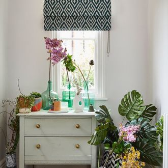 The green geo printed roman blinds hanging on the window in hallway