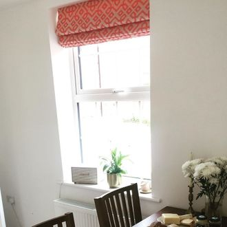 Coral and cream patterened roman blinds hanging on single hung window in dining room.