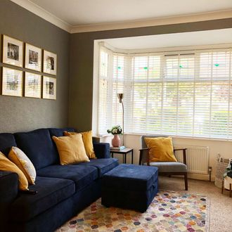 white wooden blinds hanging on windows of living room. A blue sofa decorated with mustard cushions have been placed in the room