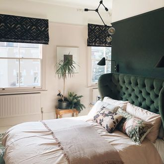 Deep green roman blinds featuring black pattern hanging in a green and white themed bedroom