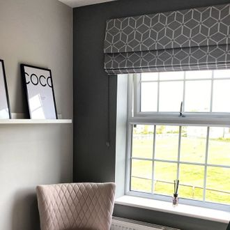 Window dressed with grey roman blind featuring geometric print in study