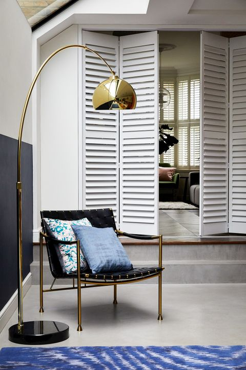 Aura White wooden shutters in living space with large golden lamp