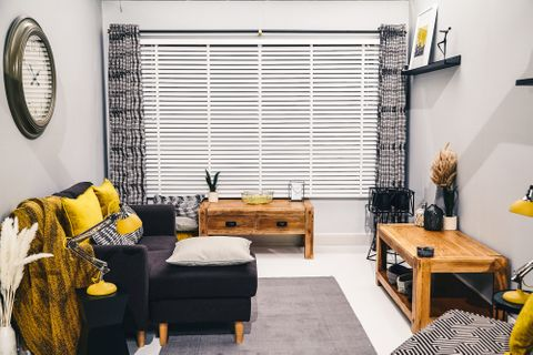 Cadillac Noir curtains with white Venetian blinds in living room