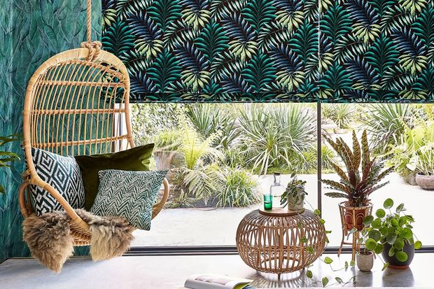 Green and yellow  printed Roman blinds over a window that has plants dotted around on the window sill.