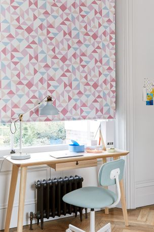 Pink and peach geo design geometric printed roller blind hanging on window of study room