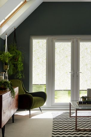 White tropical print roller blinds hanging on patio doors of living room