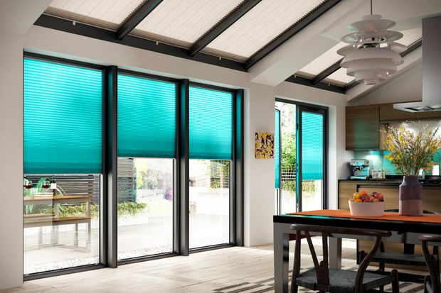 Turquoise pleated side blinds hanging on large windows and grey pleated roof blinds hanging on roof glass of kitchen
