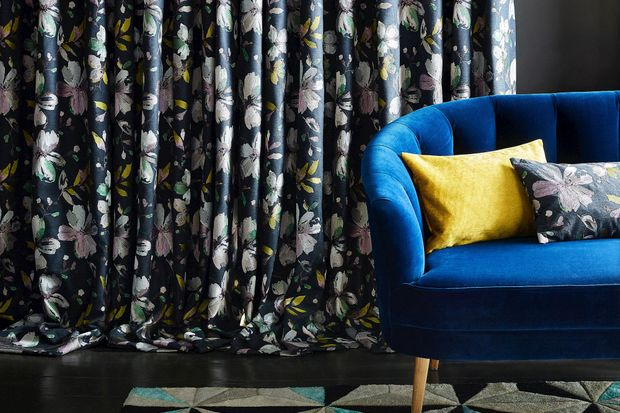 Navy blue floral curtain hanging next to blue sofa