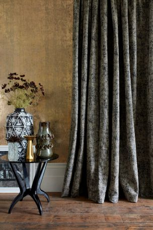 Textured white stitches over fade-out black base curtain hanging on wall in room. A coffee table with a vase is placed in the room
