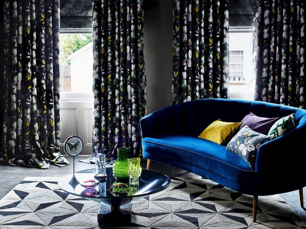 Curtain featuring multi-coloured floral embroidery on a navy background and grey roman blinds hanging on windows of a living room