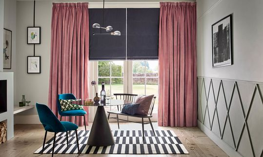 Pink velver curtains over deep blue roman blinds hanging on doors of dining room