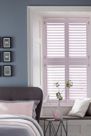Grey painted  bedroom's windows decorated with light pink shutters