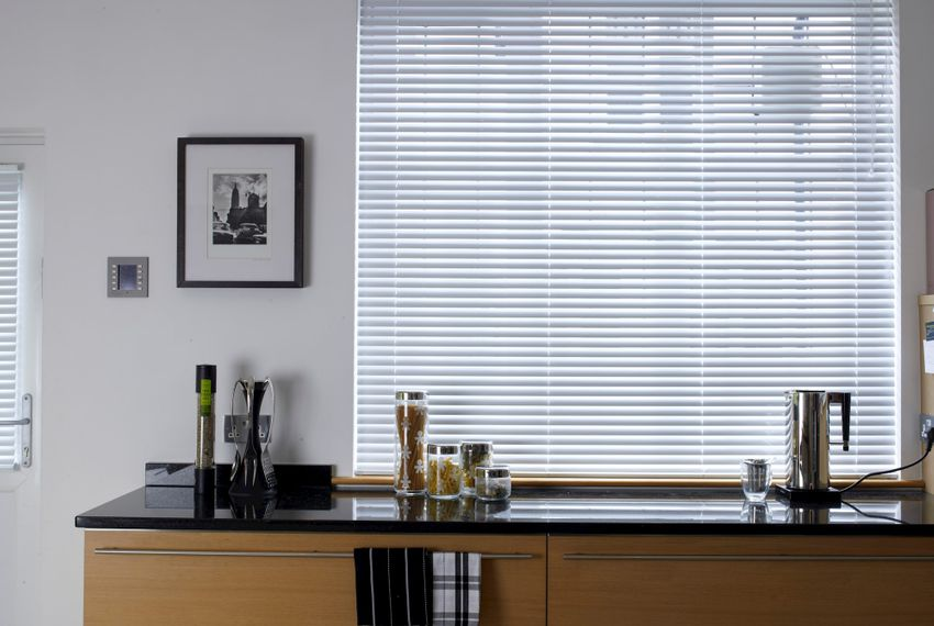metal venetian blinds in a modern kitchen window