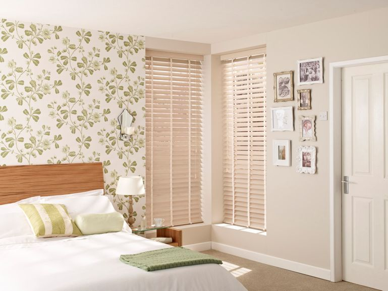 Wood coloured wood blinds fitted to a tall rectangular window in a bedroom decorated with cream and leaf patterned walls
