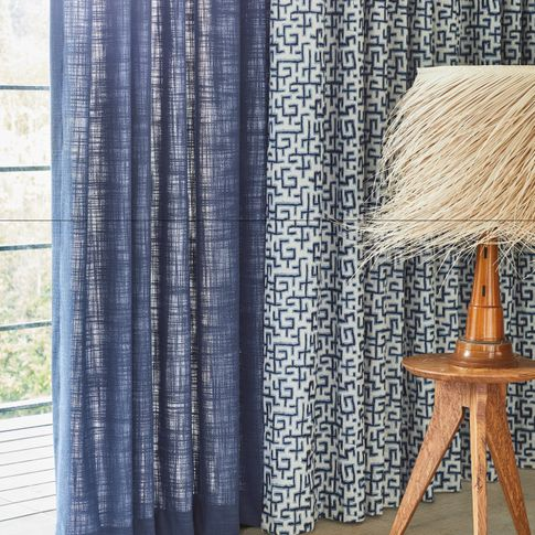 blue unlined curtain and white curtains featuring blue retro print hanging on doors in bedroom