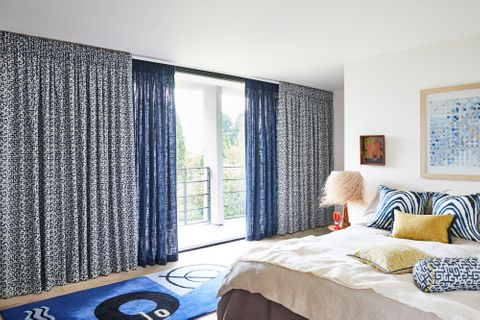 In the view white and blue retro print, plain unlined blue curtains are dressed on the sliding doors of bedroom. White and blue zebra printed cushions and citrine color plain cushion has been placed on the bed.