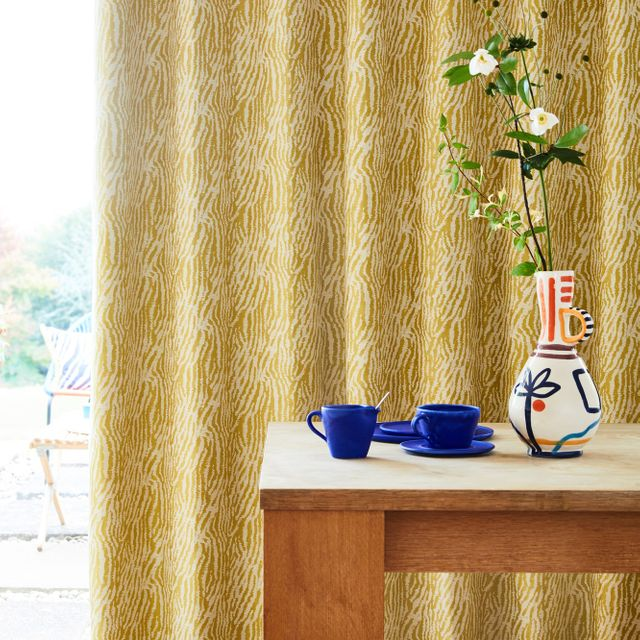 Citrine zebra print curtains hanging on the door. Blue cups and a flower vase is also placed on wooden coffee table in the corner of room.