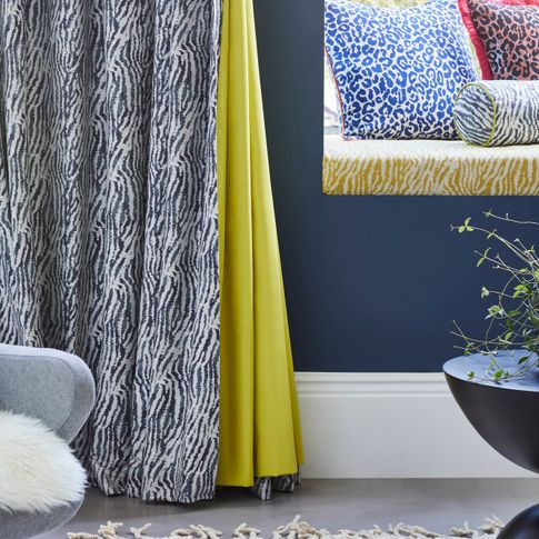 White and blue zebra print curtains with citrine lining hanging on wall. Matching Zebra print round small pillow, Blue and white Leopard print and Copper and black leopard print cushions have been placed in window seat.