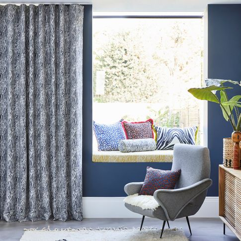 Blue and white zebra print curtains hanging on sliding doors of open plan kitchen and living area. Leopard, zebra and boho print cushions have been placed in window seat, resting chairs and on the rug