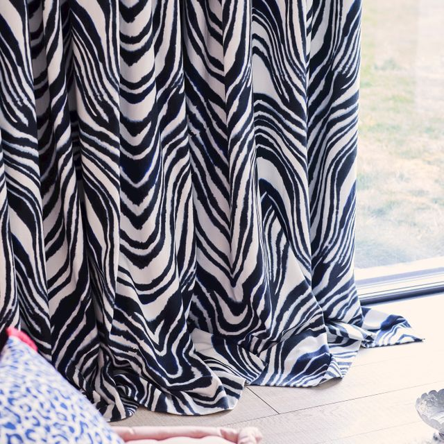 Close up of white curtains featuring some zebra print dressed on sliding door. A blue and white leopard print cushion have been placed on pink stool near the door.