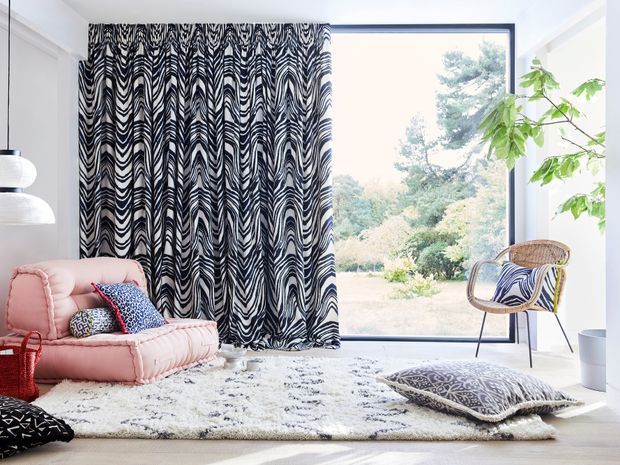 Blue and white zebra print curtains hanging on large window of garden room. Blue and white leopard print, black and white retro print, blue and white boho inspired print cushions have been placed on rug and chairs in the room.