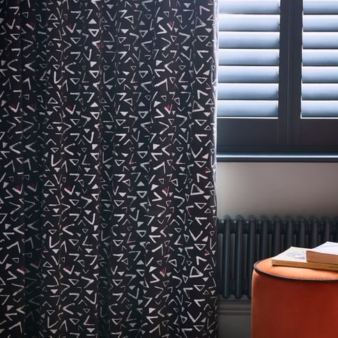 Black and white retro print curtains over black cafe style shutters in a bedroom