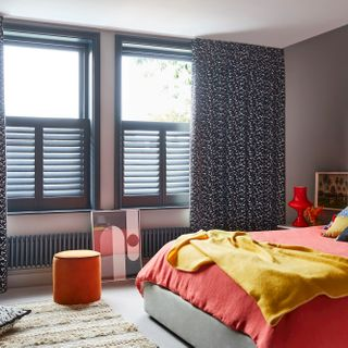 Black and white retro print curtains over grey cafe style shutters in a bedroom. Blue leopard cushion and Citrine plain cushion are placed on orange duvet on bed. White retro print cushion is resting on floor