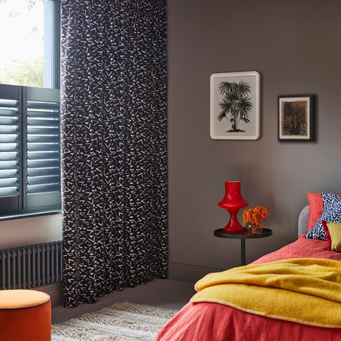 Corner view of bedroom where Black and white retro print curtains over grey cafe style shutters on windows. Blue leopard cushion and Citrine plain cushion are placed on orange duvet on bed.