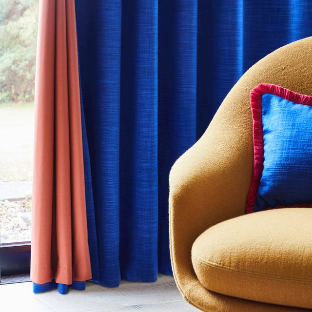 Dark blue curtain with rust color lining hanging on door, matching blue cushion with red fringe has been placed on mustard chair