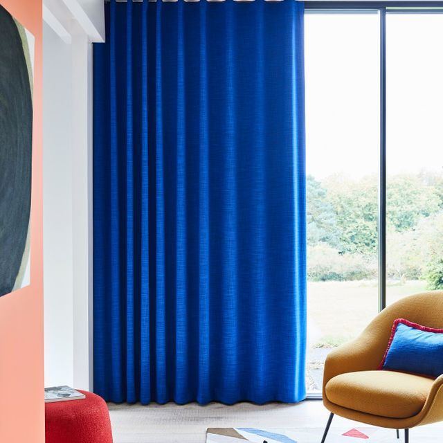 Dark blue curtains hanging on sliding doors. Matching blue cushion resting on mustard velvet chair in living room.