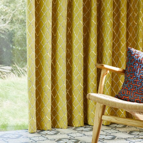 Citrine embroidered curtain on large window of garden room