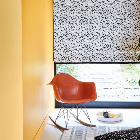 White roman blind featuring triangles in retro print hanging on window of yellow painted living room. Black retro traingle printed cushion is placed on the floor.