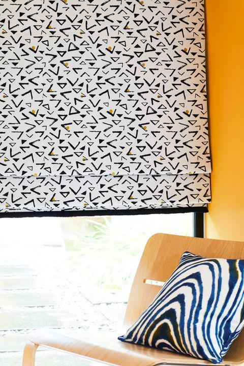 White roman blind featuring black triangles in retro print and decorated with black fringe is hanging on window of yellow painted living room. White cushion with blue zebra wavy print is placed on wooden chair in the room.
