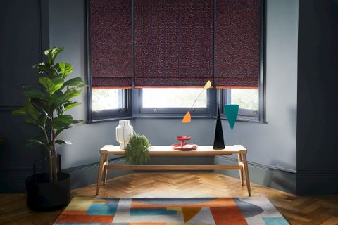 Dark  grey roman blinds featuring bright orange boho inspired embroidery dressed on windows in living room. Blinds are decorated with orange fringe.