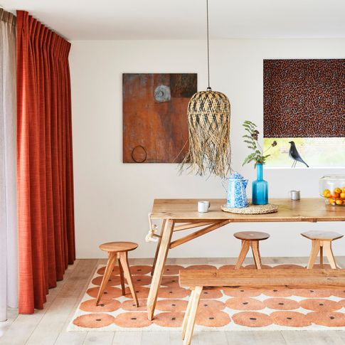 Orange curtians and white voile curtains are hanging on slding doors of dining room. Boho Inspired black orange printed roman blinds are dressed on the windows in the room.