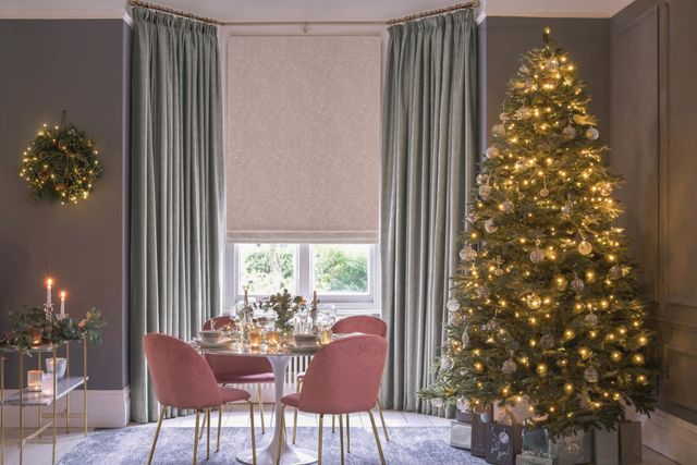 Green curtains over beige roman  blinds dressed on windows of dining room. Room is decorated with a big christmas tree