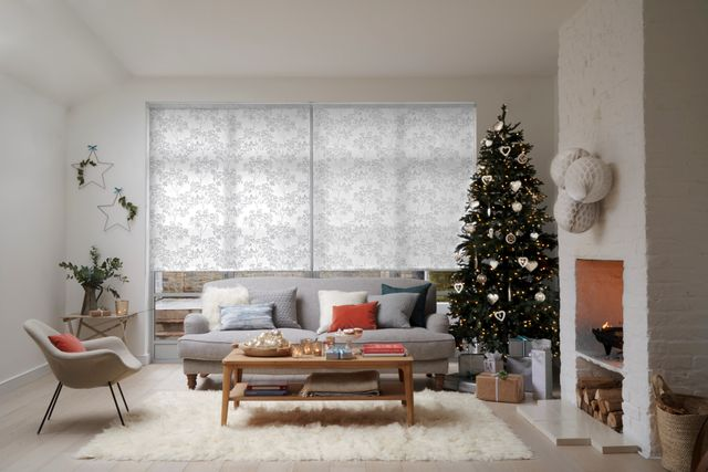 View of a living room decorated with grey sofa, christmas tree, candles. Windows of room are dressed with silver tree printed roller blinds