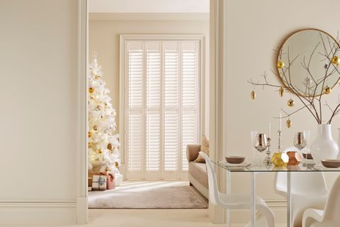 Full height white shutters installed on single large window of living room, room is decorated with white christams tree