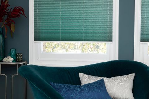 Green Pleated blinds from House Beautiful range dressed on windows in living room. Green velvet sofa has been placed by window.