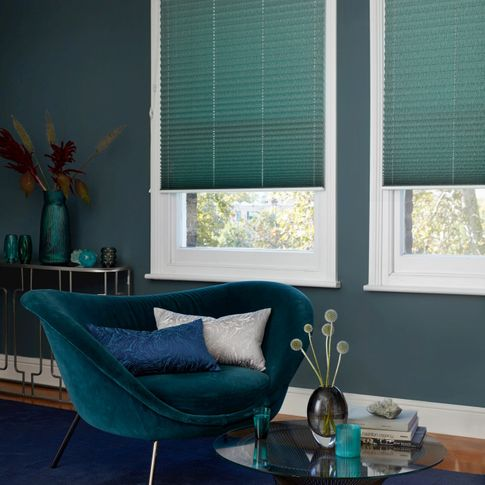 House Beautiful green Pleated blinds dressed on windows in living room. A velvet sofa has been placed near window, with a blue and a silver cushion.