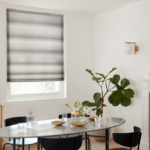Side view mini stripe grey Pleated blinds from House Beautiful range hanging on single window in dining room. Grey dining table, four dark grey chairs in front and large green plant in corner.