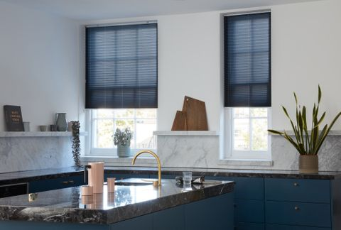Blue Pleated blinds dressed on two kitchen windows. Blinds are matching colour to the cupboards and drawers of kitchen, with a peach jug accessory.