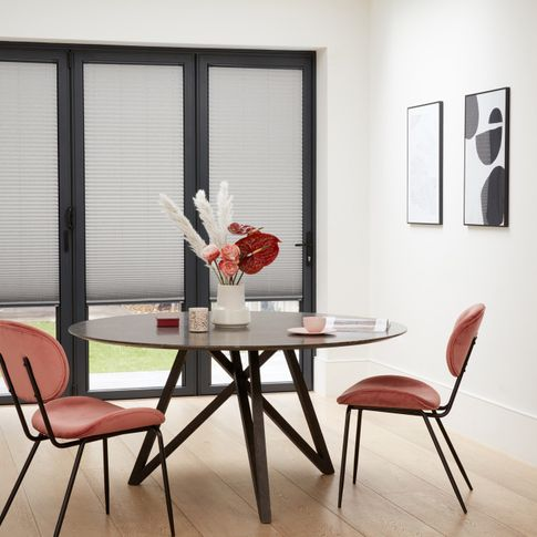 Grey Micro Pleat Pleated blinds dressed on bi-fold doors of dining room. Round table along with pink chairs have been placed in the room.
