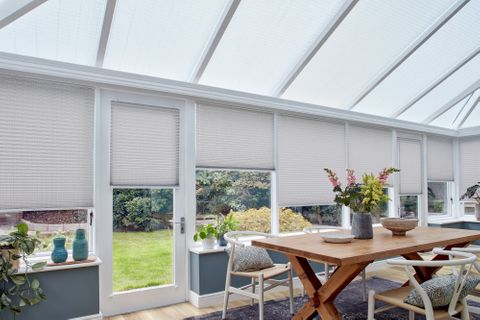 Grey motorised Pleated blinds dressed on windows of large conservatory. A large garden table along with chairs have been placed in conservatory.