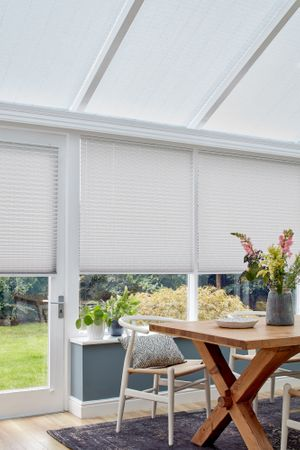 Grey motorised Pleated blinds dressed on windows of conservatory. An informal wooden table and relaxed dining chair sits on a grey rug.