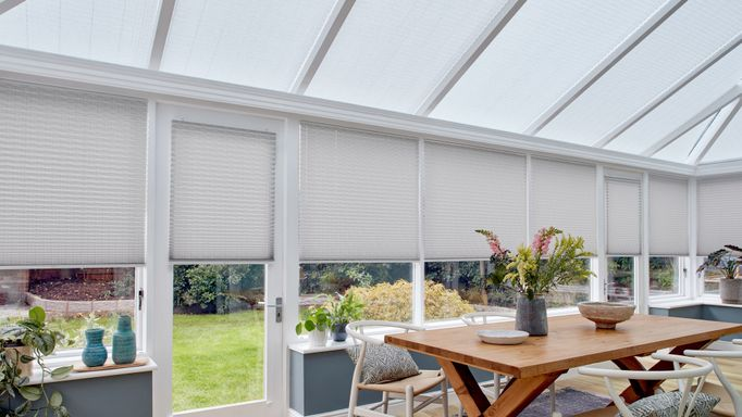 Grey motorised Pleated blinds dressed on windows of large conservatory. A large  table and chairs have been placed in conservatory, with several plants.