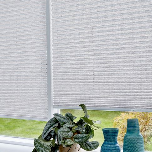 Close up of light grey Pleated blinds dressed on conservatory windows.