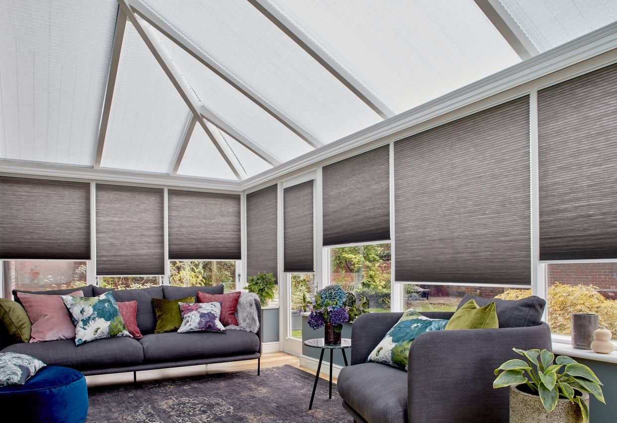 Charcoal Thermashade Pleated blinds at varying drop heights dressed on the windows in conservatory. Grey sofa with  cushions is placed in conservatory.