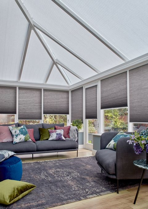 Charcoal Thermashade Pleated blinds at varying drop heights dressed on the windows in conservatory. Grey sofa with cushions and a large grey rug are also in situ.