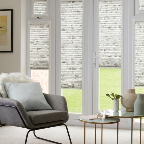 Duo natural Thermashade Perfect Fit Pleated blinds from House Beautiful range dressed on bi-fold doors, at varying drop heights. A grey upholstered chair and cushions are also in the room.